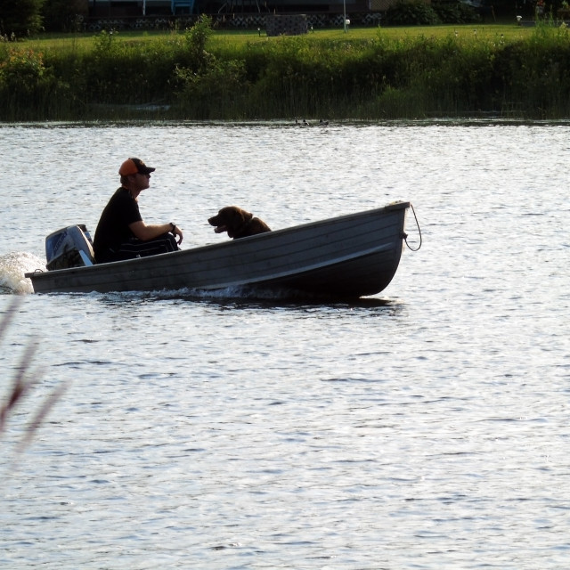 """""""Man and dog in boat"""" stock image"""