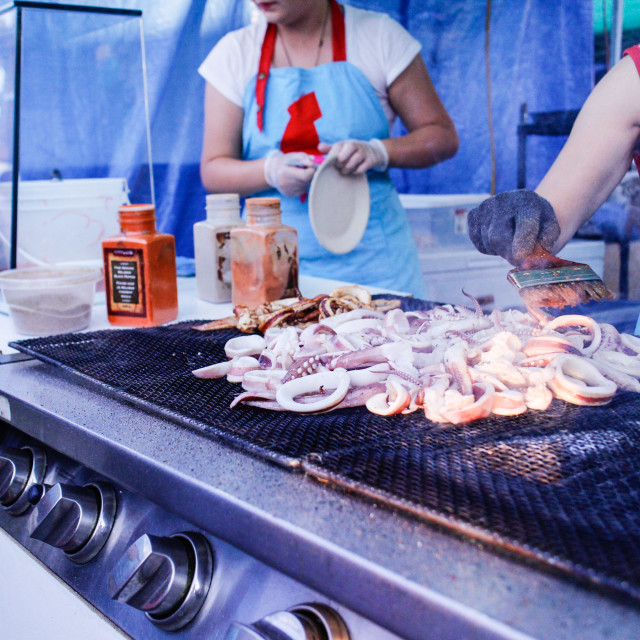 """""""Grilling squid at the market"""" stock image"""