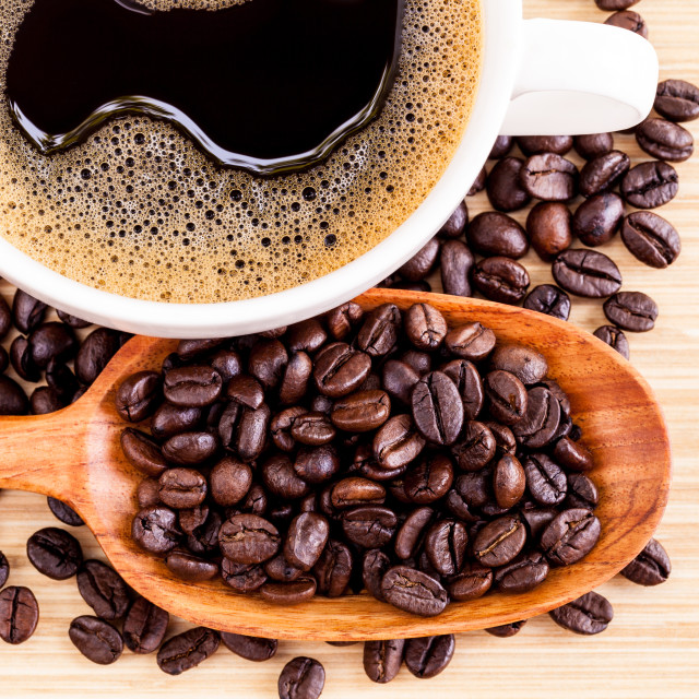 """A Coffee cup and coffee beans on wooden panel - With copy space"" stock image"