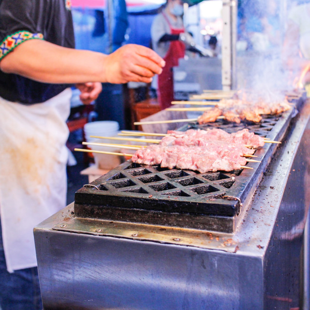 """Grilling lamb skewers at night market"" stock image"