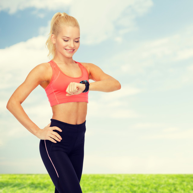 """smiling woman with heart rate monitor on hand"" stock image"