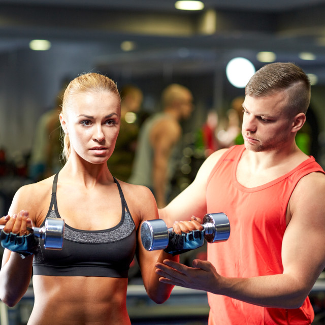 """young couple with dumbbells flexing muscles in gym"" stock image"