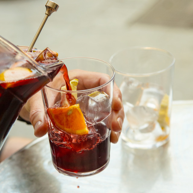 """Sangria being poured into glass full of ice cubes and fruit"" stock image"