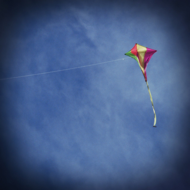 """Kite Flying against Blue Sky"" stock image"