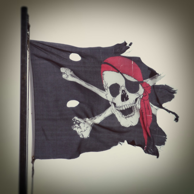"""Torn and Ripped Jolly Roger Flag"" stock image"