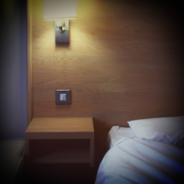 """""""Bedside Table and Lamp in Motel Room"""" stock image"""