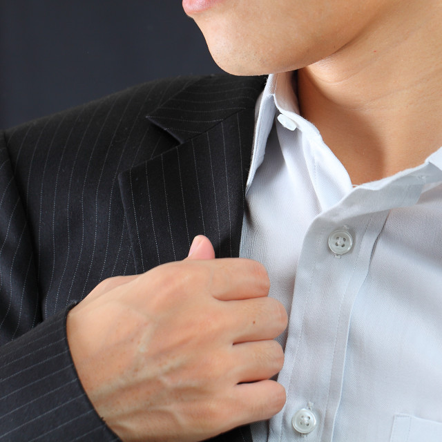"""""""young man adjusting his suit on a black background"""" stock image"""