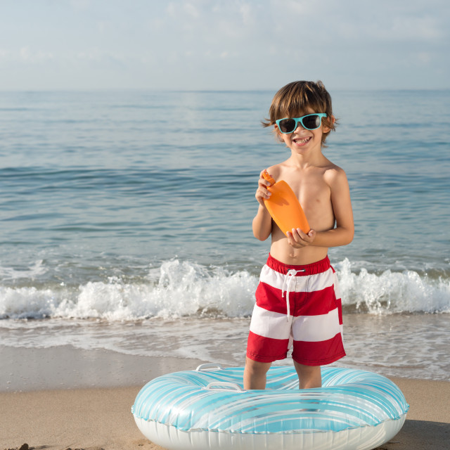 """child with sun protection spray in the beach"" stock image"