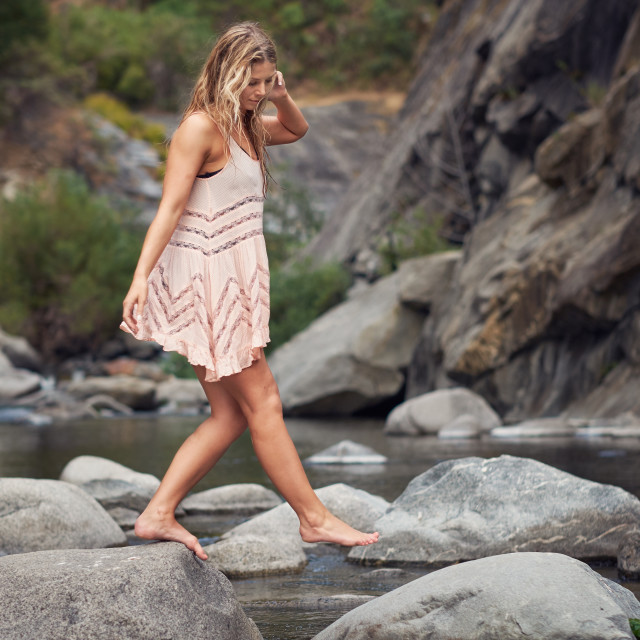 """A Barefoot Woman in a Summer Dress Walking Across a Creek."" stock image"