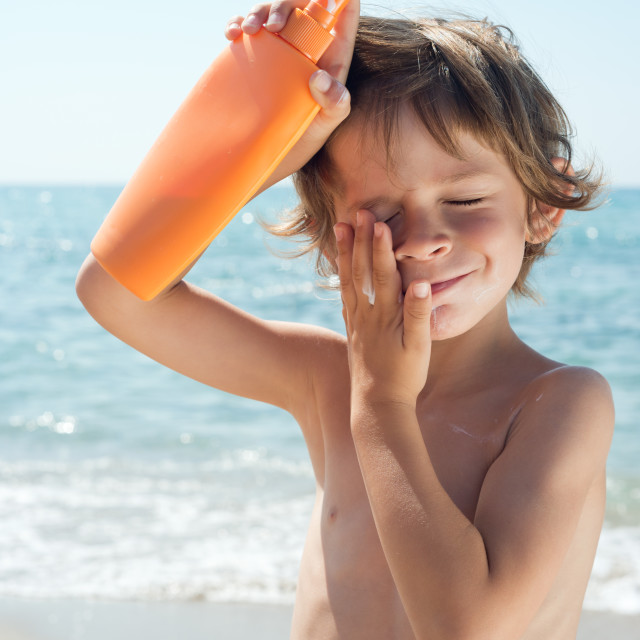 """child apply sun cream on his face with hands"" stock image"