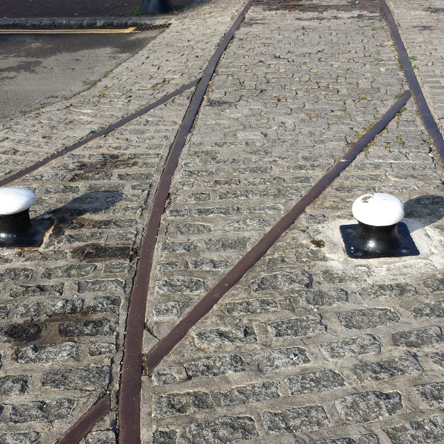 """Rails, bollards and cobbles"" stock image"