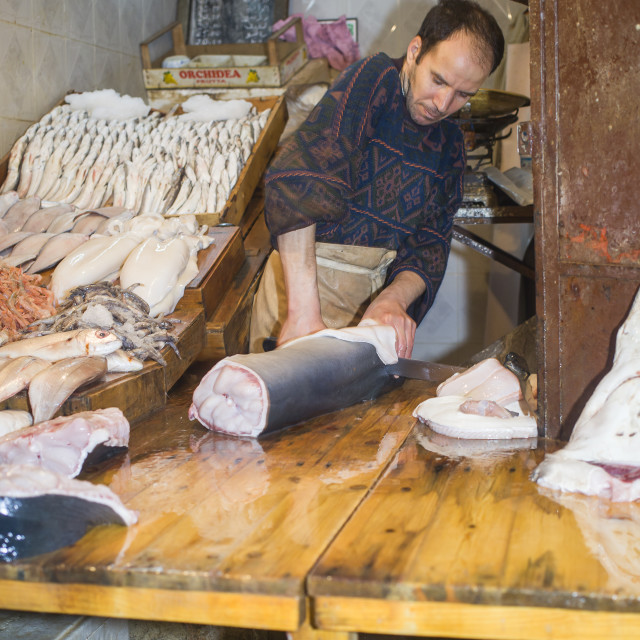 """Fish monger cutting shark at his store in in Fez"" stock image"