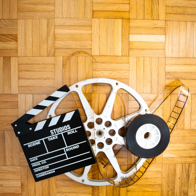 """Movie clapper board and film reel on wooden floor"" stock image"