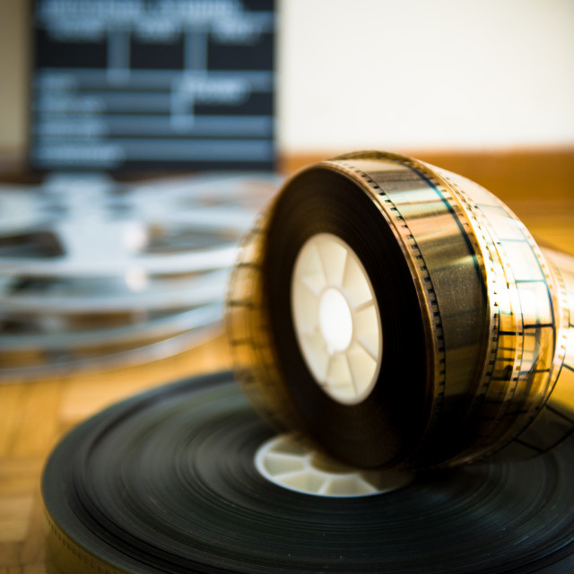 """Cinema film reel and out of focus movie clapper board"" stock image"
