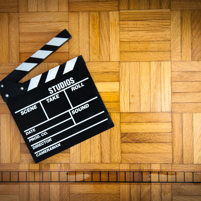 """Movie clapper board and filmstrip reel on wooden floor"" stock image"