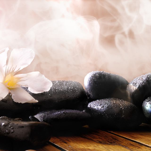"""Group of black stones on wood base with steam background"" stock image"