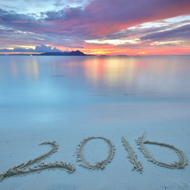 """Numbers 2016 written on sandy beach during sunset."" stock image"