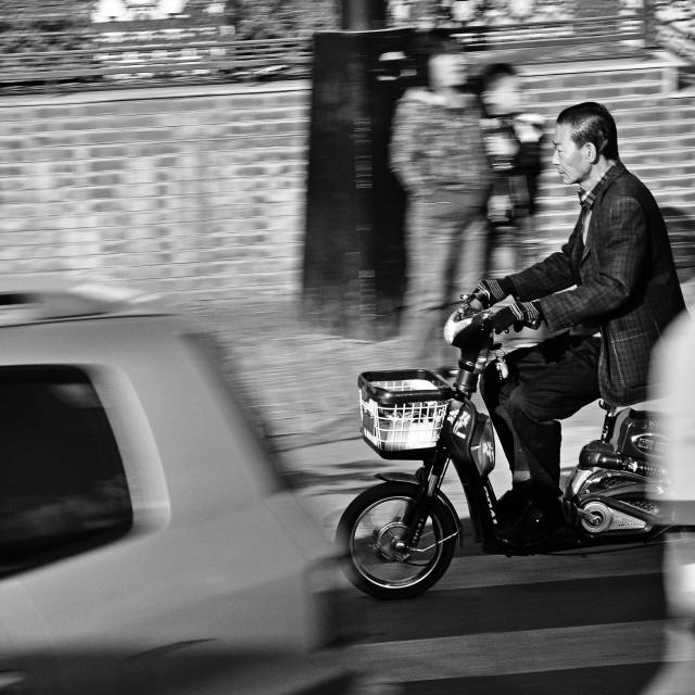 """Panning of Asian man on a bike"" stock image"
