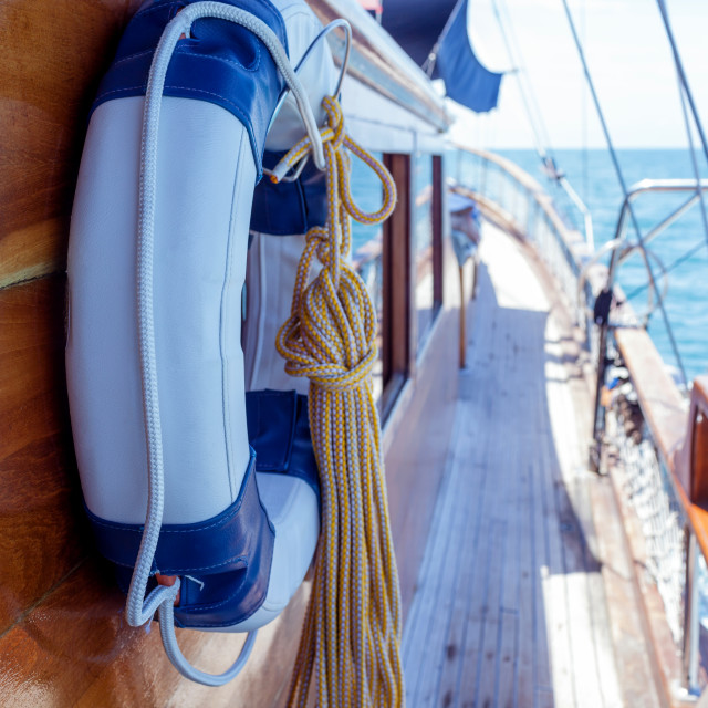 """Lifebuoy on the wall of sailboat with rope."" stock image"