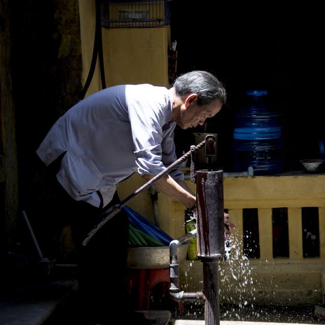 """""""Vietnamese man at a water pump."""" stock image"""