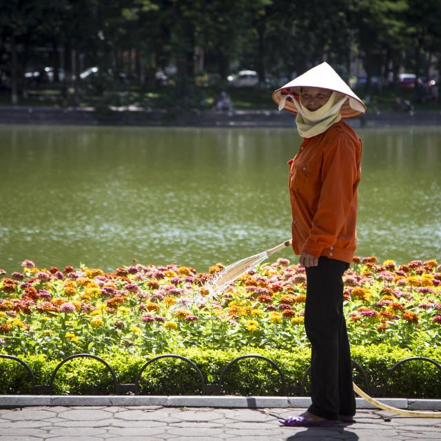 """""""Lady watering flowers in Vietnam."""" stock image"""