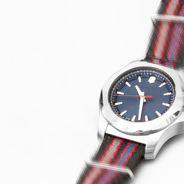 """A blue dial watch on a colourful strap looks as if it is moving"" stock image"