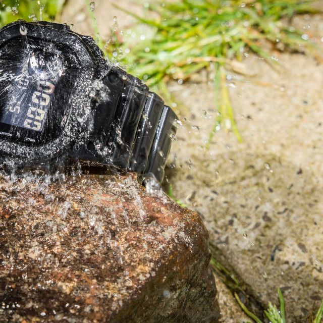 """Water splashes on a rugged wristwatch"" stock image"