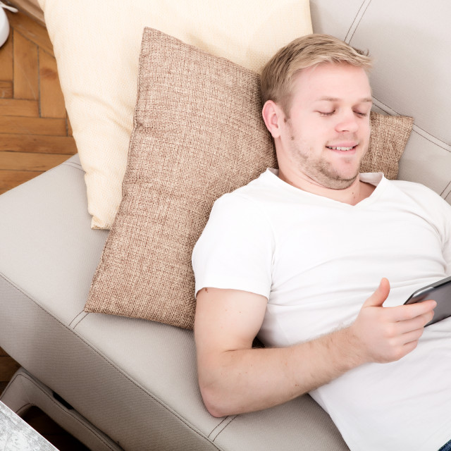 """""""Young man with a Tablet PC on the Sofa"""" stock image"""