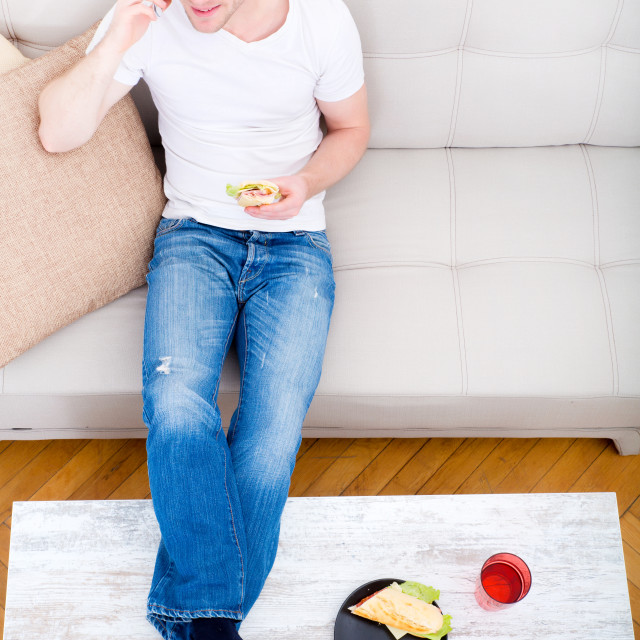 """""""Young man with a Sandwich on the Sofa"""" stock image"""