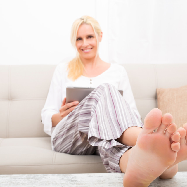 """""""Woman with Tablet pc on the sofa"""" stock image"""