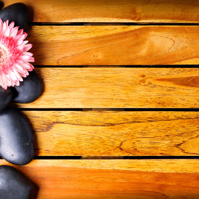 """Black stones and flower on the left side on wooden"" stock image"