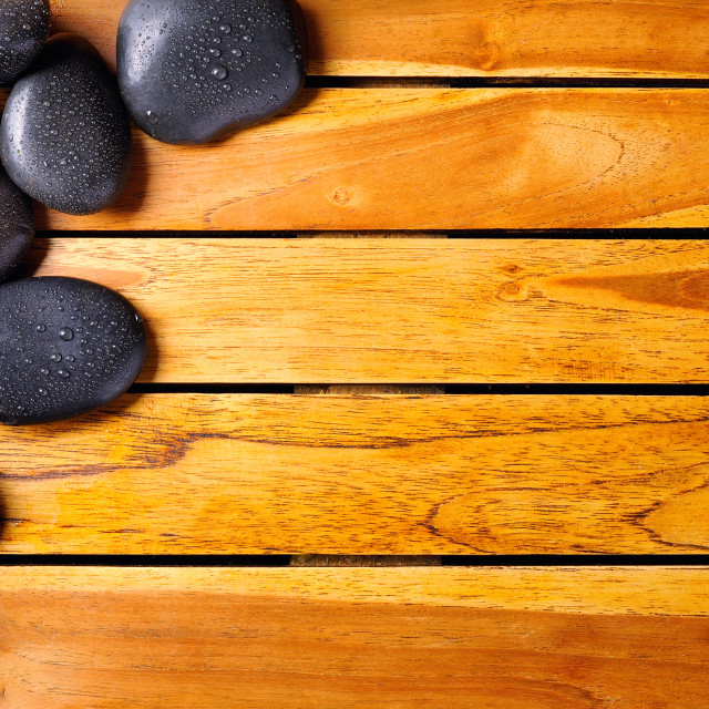 """Stones with drops in the top left corner on wooden"" stock image"