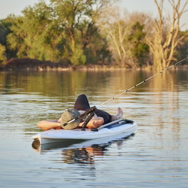 """Fisherman Sleeping on a Paddle Board"" stock image"