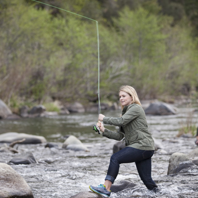 """Woman Fishing in a River"" stock image"