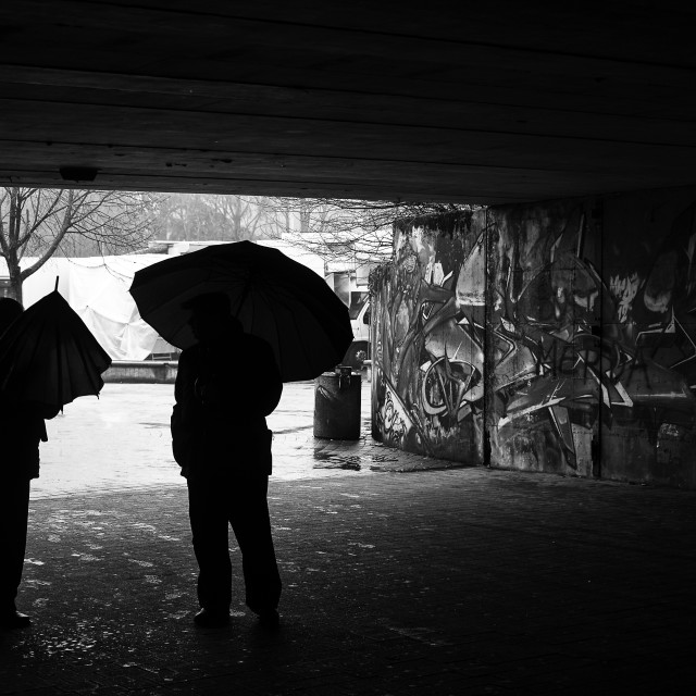 """""""Black and white image of two people with umbrellas outdoor"""" stock image"""