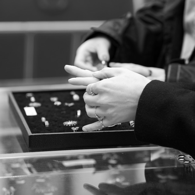 """Black and white image of woman measuring rings in shop"" stock image"