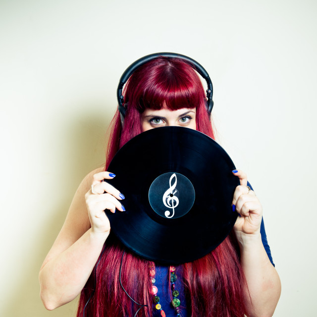 """Young pretty woman looking with headphones and vinyl record"" stock image"