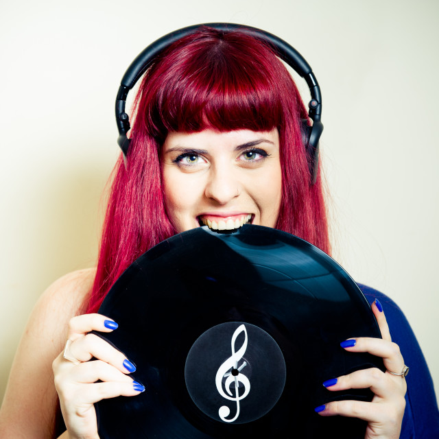 """Young pretty woman smiling and biting vinyl record close up"" stock image"