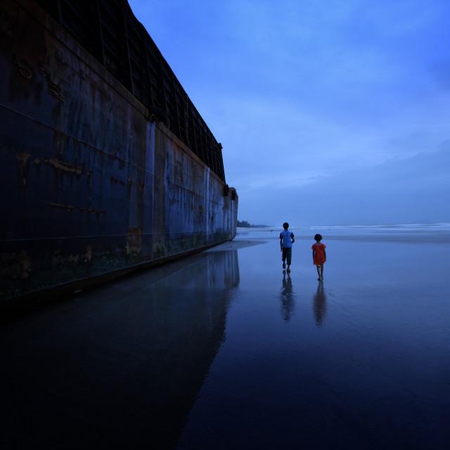 """2 kids at beach near big barge"" stock image"