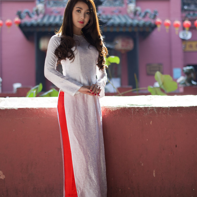 """Vietnamese girl wearing Ao dai praying in pagoda"" stock image"