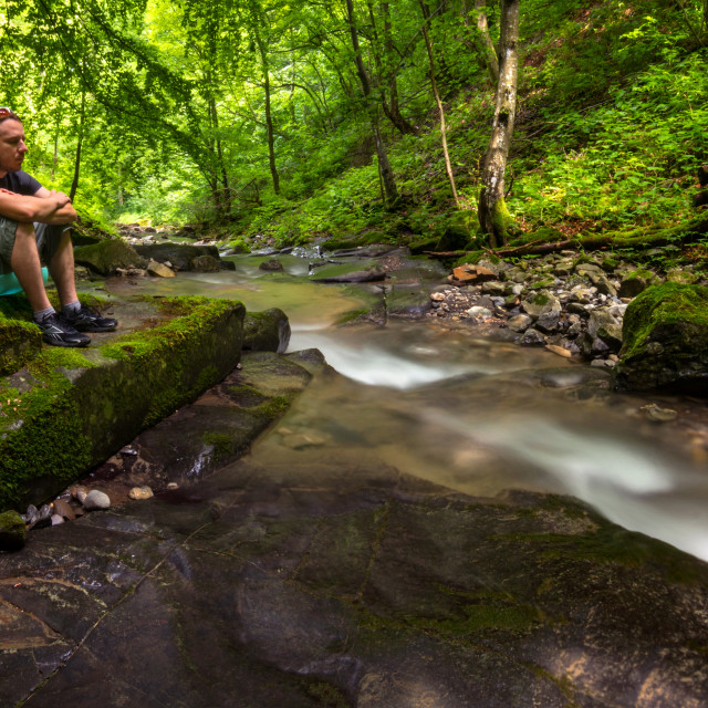 """Man meditating near forest stream"" stock image"