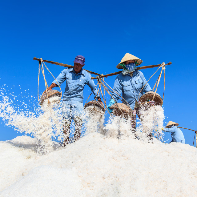 """Workers transporting salt from the fields in Hon Khoi, Viet Nam"" stock image"