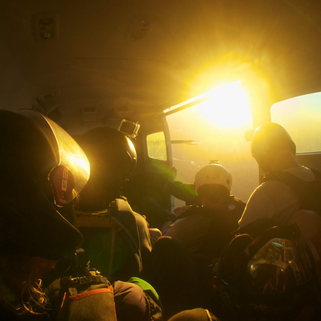 """Sunlight illuminates a plane full of skydivers"" stock image"