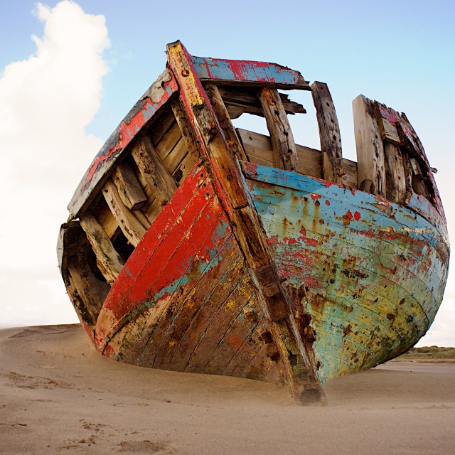 """Boat ruins in the sand"" stock image"