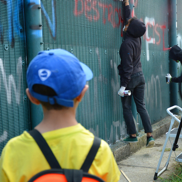 """Young boy looking on to graffiti"" stock image"