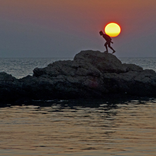"""Man carrying setting sun"" stock image"