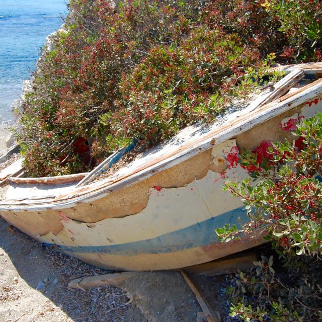 """An abandoned little fishing boat on Greek beach"" stock image"