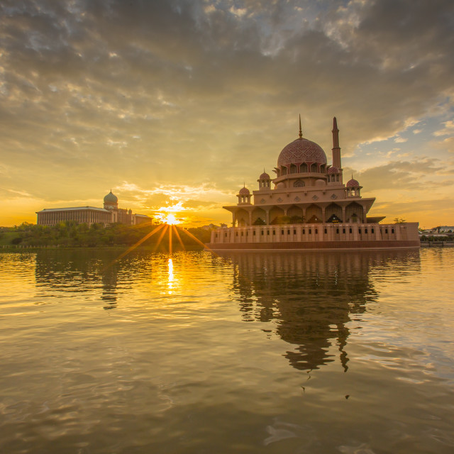 """Sunburst sunlight during sunrise at Putra Mosque, Putrajaya"" stock image"