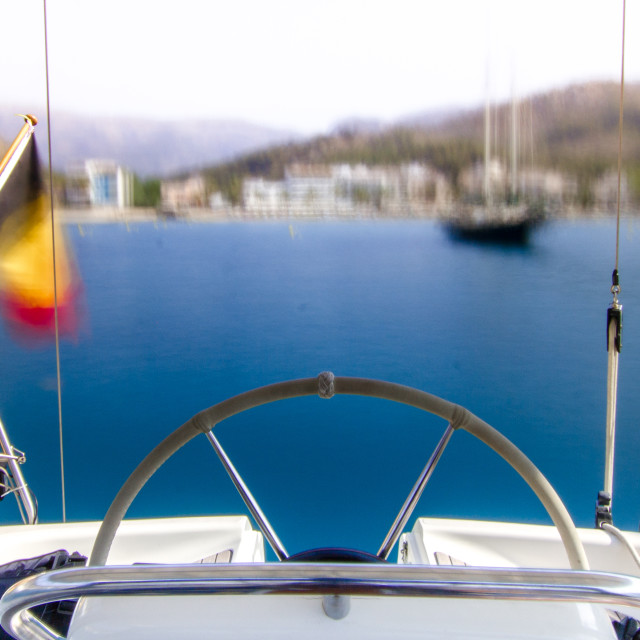 """""""Sailing boat cockpit with a motion blurred bay in the back."""" stock image"""