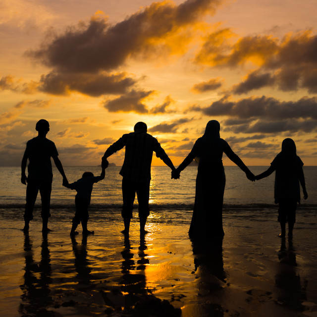 """Silhouette of happy family at the beach"" stock image"